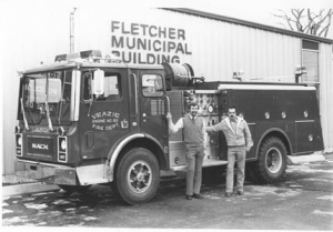 Old photo of two men in front of a fire truck